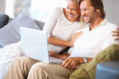 Buy stock photo Cheerful mature man and woman looking at laptop screen on couch at home