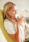 Side view of a mature woman in happy thoughts drinking tea