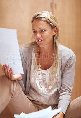 Buy stock photo Portrait of a relaxed mature woman sitting on floor and reading document