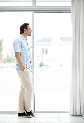 Buy stock photo Full length image of a young man standing near a window - Indoor