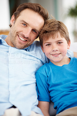 Buy stock photo Portrait of a handsome young man and his son relaxing together at home - Indoor