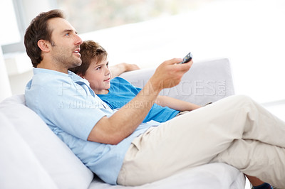 Buy stock photo Portrait of a man with remote control and his son sitting together watching television at home - Indoor