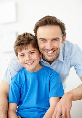 Buy stock photo Portrait of a handsome young father with his son sitting together and smiling - Indoor
