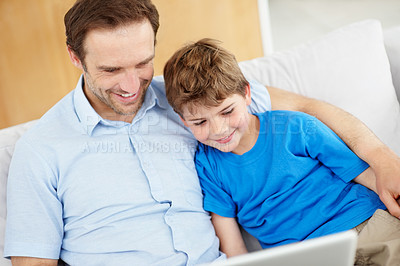 Buy stock photo Portrait of a happy young father and his son sitting together on sofa and using laptop - Indoor