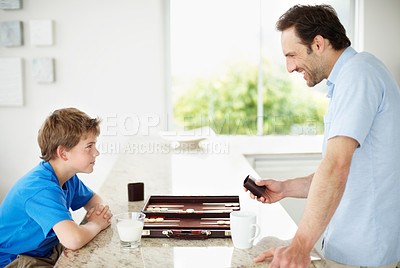 Buy stock photo Portrait of a happy young father and son on kitchen counter playing backgammon - Indoor