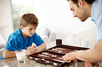 Father and son playing backgammon game in kitchen
