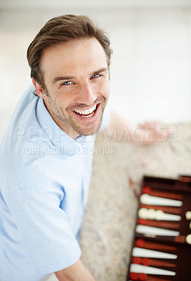 Buy stock photo Portrait of a happy young man playing backgammon game - Indoor
