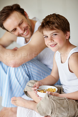 Buy stock photo Portrait of a happy young boy eating a healthy breakfast with his father in background