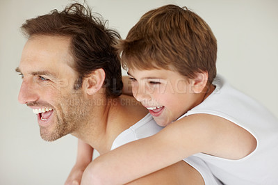 Buy stock photo Portrait of a happy father giving piggyback ride to his son and looking at something interesting