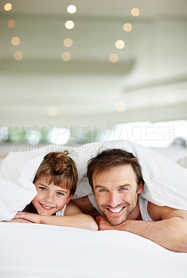 Buy stock photo Portrait of happy young father and son together under bedsheet smiling - Copyspace