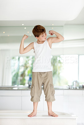Buy stock photo Portrait of a young boy standing on kitchen counter and looking at his muscles - copyspace