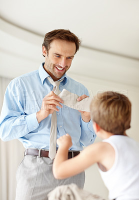 Buy stock photo Portrait of a happy young father showing his new necktie to his son - Indoor