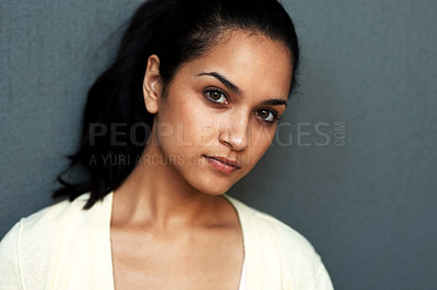 Buy stock photo Closeup portrait of a pretty young woman looking at you with an attitude against grey background