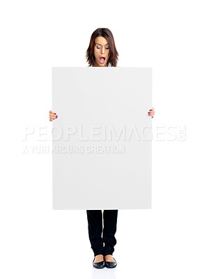 Buy stock photo Portrait of a pretty surprised young woman looking at empty white board over white background