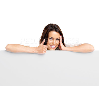 Buy stock photo Portrait of an attractive smiling woman leaning on blank board with thumbs up against white background