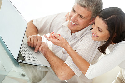 Buy stock photo Portrait of a mature couple browsing the internet on a laptop