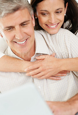 Buy stock photo Portrait of a happy mature man working on laptop wife hugging him from back