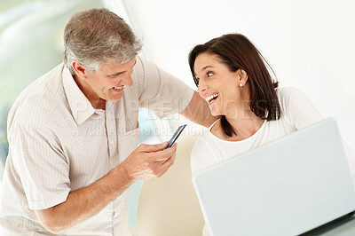 Buy stock photo Portrait of happy mature couple using their credit card to shop from the internet