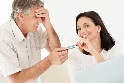 Buy stock photo Portrait of mature man looking worried while giving credit card to his wife for shopping online