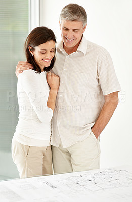 Buy stock photo Portrait of happy mature couple looking at new house plan and smiling