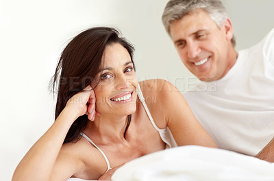 Buy stock photo Closeup portrait of a smiling beautiful mature woman lying in bed and husband in the background