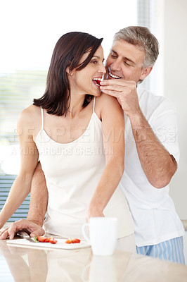 Buy stock photo Portrait of happy romantic mature man feeding fruits to his beautiful wife