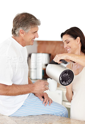 Buy stock photo Portrait of a happy mature woman pours tea to her husband in kitchen
