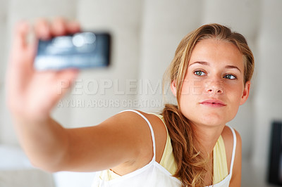 Buy stock photo Portrait of a cute young woman taking picture of herself through her mobile phone