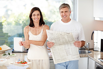 Buy stock photo Portrait of mature man in kitchen with newspaper and wife making breakfast