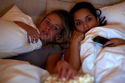 Buy stock photo Portrait of afraid young females watching a horror movie while lying on the bed