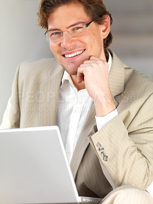 Buy stock photo Portrait of a cheerful young businessman with hand on chin. Working on a laptop in an urban city scene.