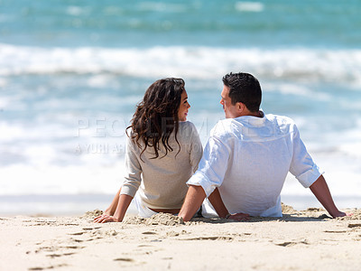 Buy stock photo Young couple sitting together on beach
