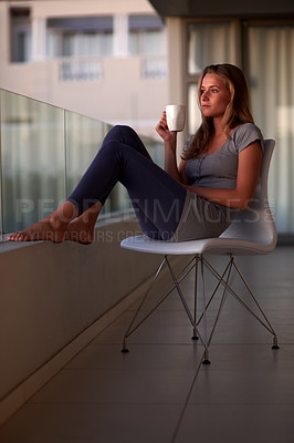 Buy stock photo Portrait of a lovely young woman looking away with a cup of coffee while sitting on chair at home
