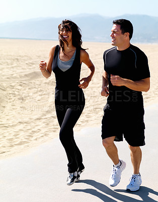 Buy stock photo Full length of a happy young couple jogging on beach