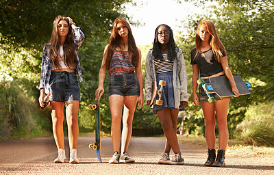 Buy stock photo Four teenage girls standing outdoors with their skateboards