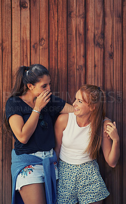 Buy stock photo Two young friends standing outdoors sharing secrets