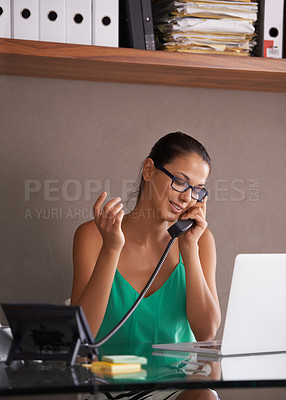 Buy stock photo A pretty young woman sitting at her desk making phone calls