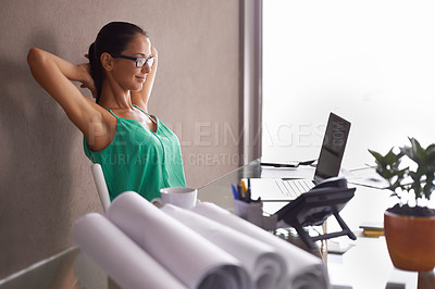 Buy stock photo A young woman stretching in her seat as the day comes to an end
