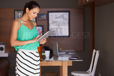 Buy stock photo A young office worker using a digital tablet to do some work