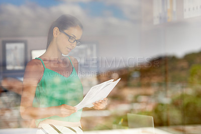 Buy stock photo A woman standing at home reading through paperwork