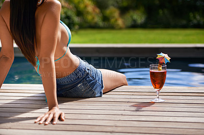 Buy stock photo An attractive young woman relaxing beside a swimming pool with a cocktail