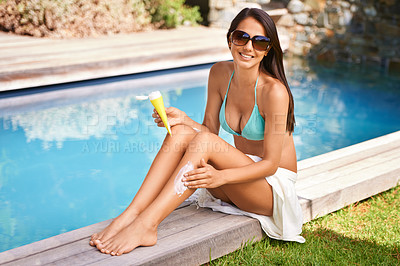 Buy stock photo A beautiful woman applying sunscreen to her legs while sitting by the pool