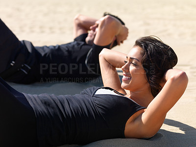 Buy stock photo Side view of a young couple exercising on the beach together