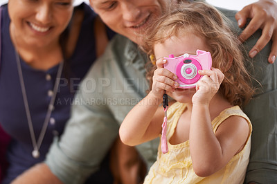 Buy stock photo A little girl playing with a camera as she sits with her parents