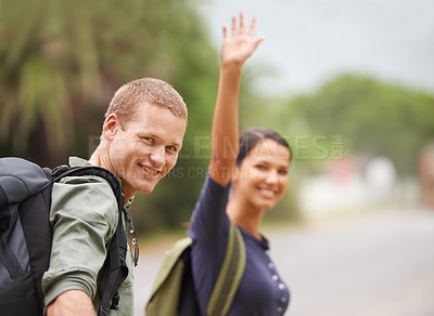 Buy stock photo A cute couple calls a cab as they stand on the side of a road