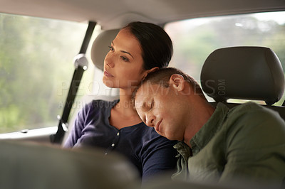Buy stock photo An exhausted man sleeps on his wife's shoulder while they travel in a car