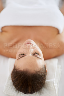 Buy stock photo Shot of a beautiful young woman lying on her back on a massage table