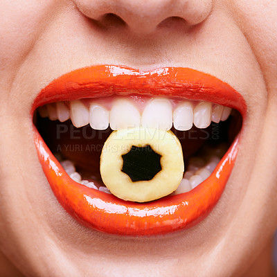 Buy stock photo Cropped shot of a beautiful young woman eating a liquorice sweet
