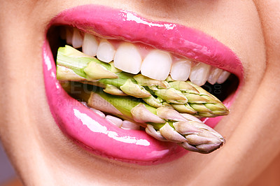 Buy stock photo Cropped shot of a woman biting on a bunch of asparagus