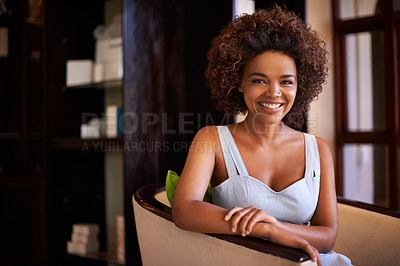 Buy stock photo Shot of a young woman sitting on a chair